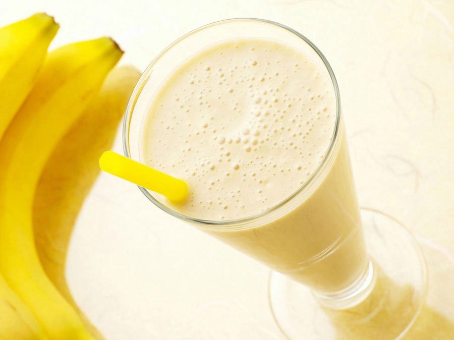 Banana milkshake on a glass with a straw.
