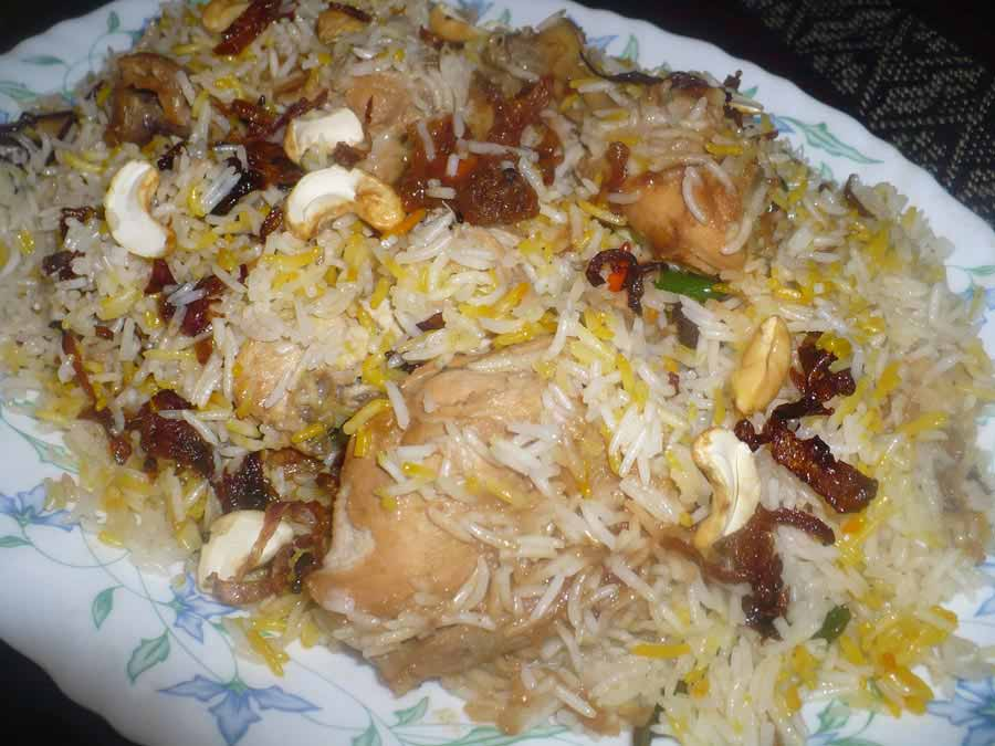 Decorated chicken biriyani in a plate with almond
