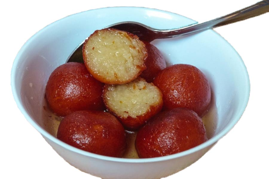 Few piece of golap jam on a bowl. One of them are cut off.