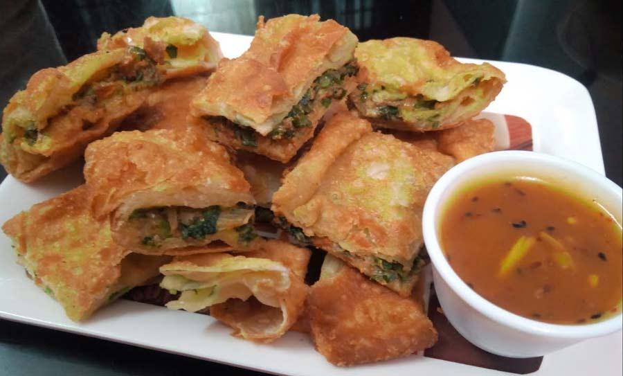 Moglai parota over a tray with sauce