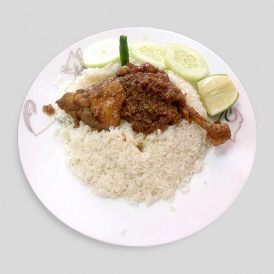 Traditional morog polao served over a plate with leg piece and vegetables.