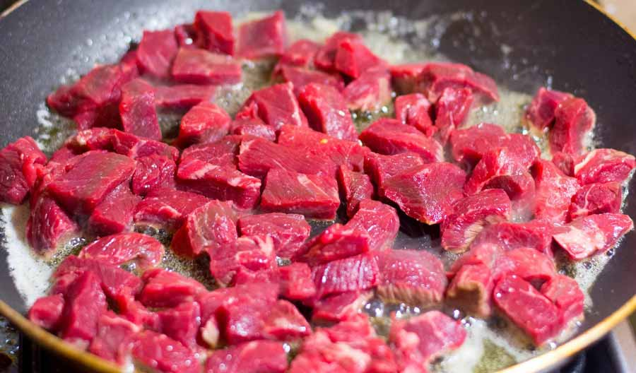 Beef are frying on a pan with oil.